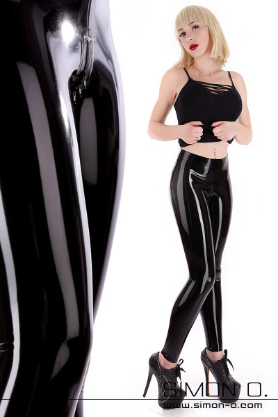 A blonde woman with tight fitting shiny black latex leggings. She wears a top and high heels combined with it.