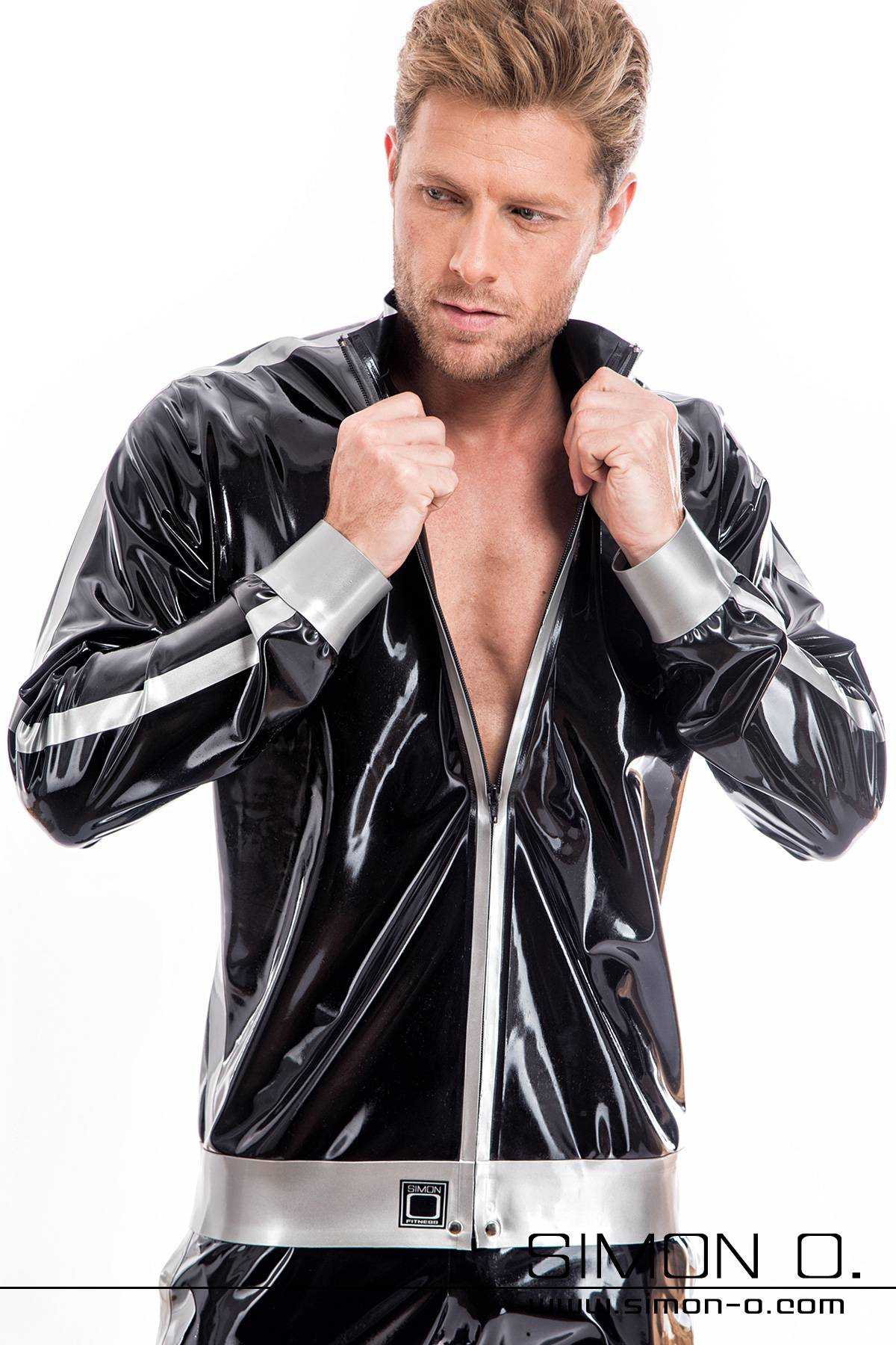 A man wears a shiny latex jacket with pockets in black and Simon O. Logo on the stand-up collar.