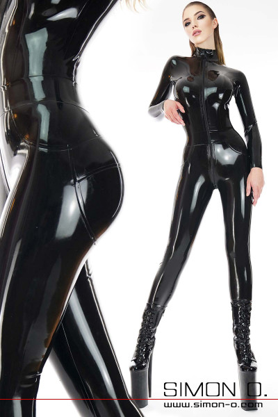 A model wears a skintight latex overall in black. The overall has a zipper in the front through the crotch.