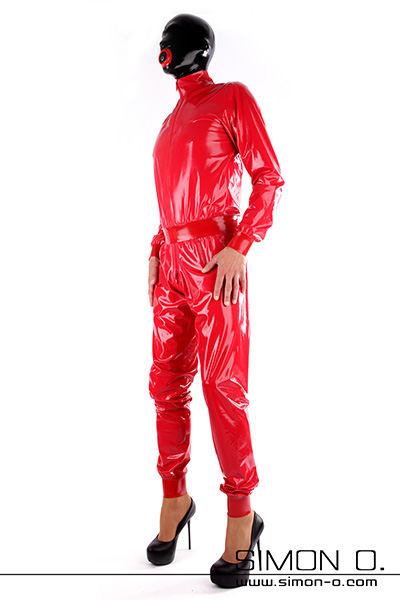 A man in a red loose latex suit with cuffs on arms and legs. He wears high heels a mask socks and gloves made of latex