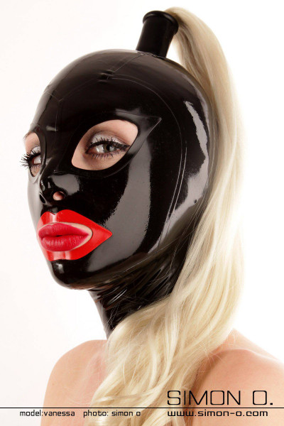 A woman wears a shiny latex hood in black with red mouth and hairpiece in blond
