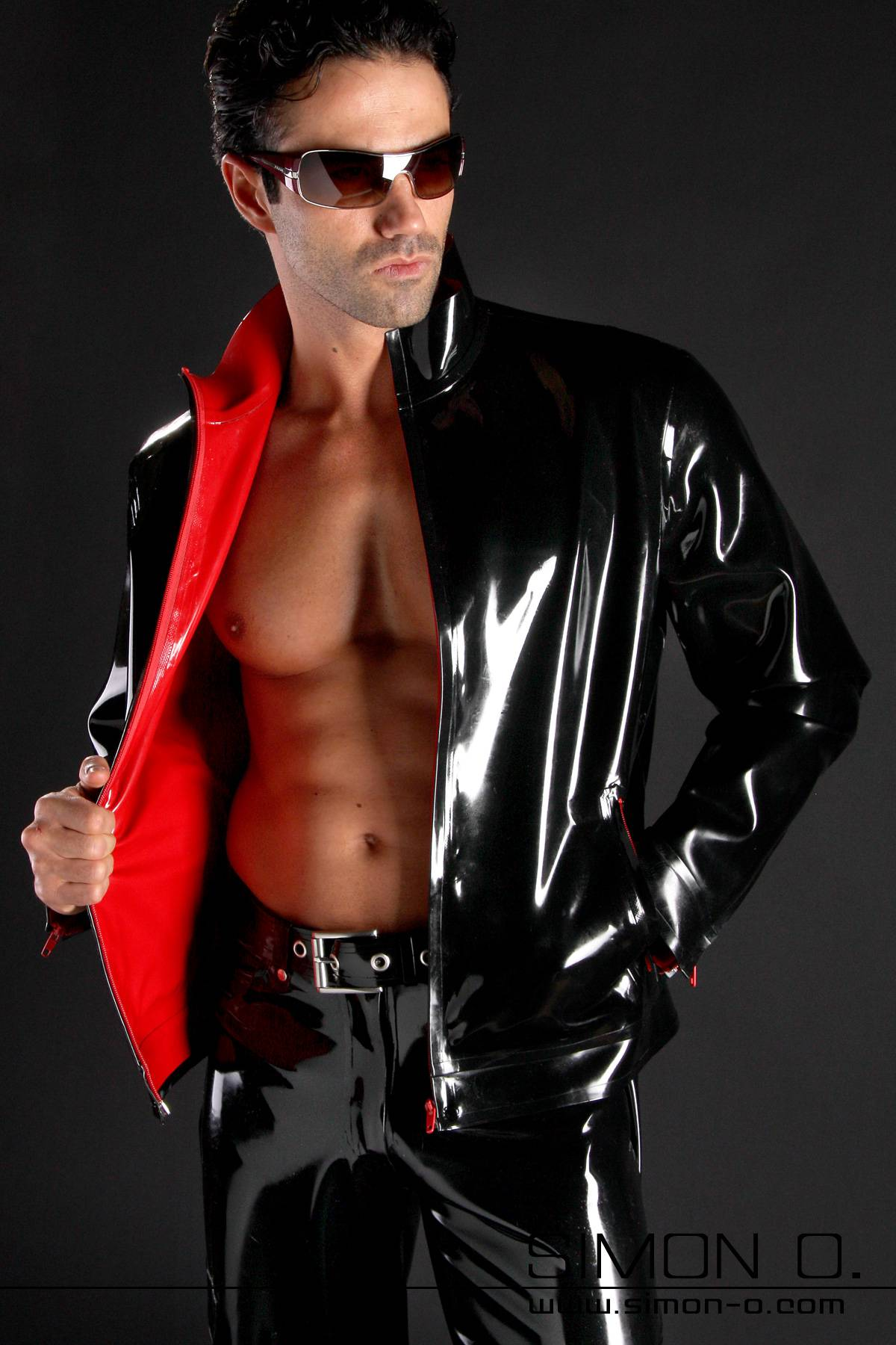 A man wears a black shiny latex jacket with red latex lining