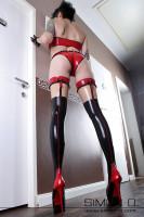 Vorschau: Eine schlanke Frau trägt ein sexy glänzendes Latex Unterwäsche Set in Schwarz mit Rot kombiniert bestehend aus Latex Slip, BH, und Latex Strümpfen