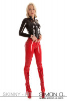 Preview: Blonde woman with extreme platform high heels dressed in tight red latex pants and a latex shirt in black