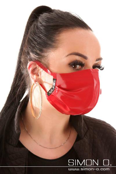 Eine Faru trägt einen Mund und Nasenschutz aus Latex in Rot