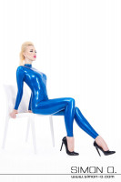 Preview: Woman sitting on an armchair wearing a shiny latex suit with black high heels