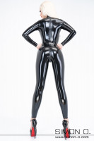 Preview: A woman with a wrinkle-free sitting shiny latex catsuit in black - with a zipper in the crotch seen from behind.