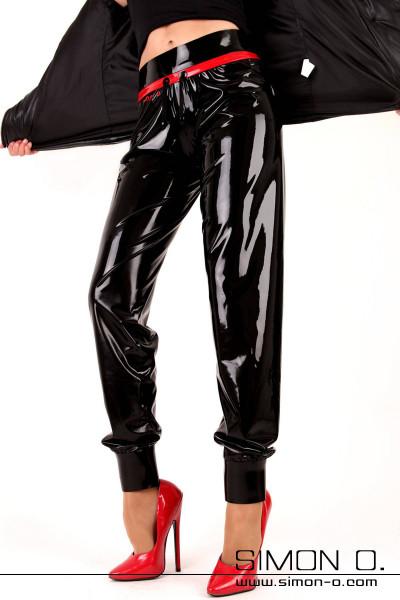 Eine Frau trägt eine Latex Glanz Joggings Hose in Schwarz mit Rot und rote High Heels